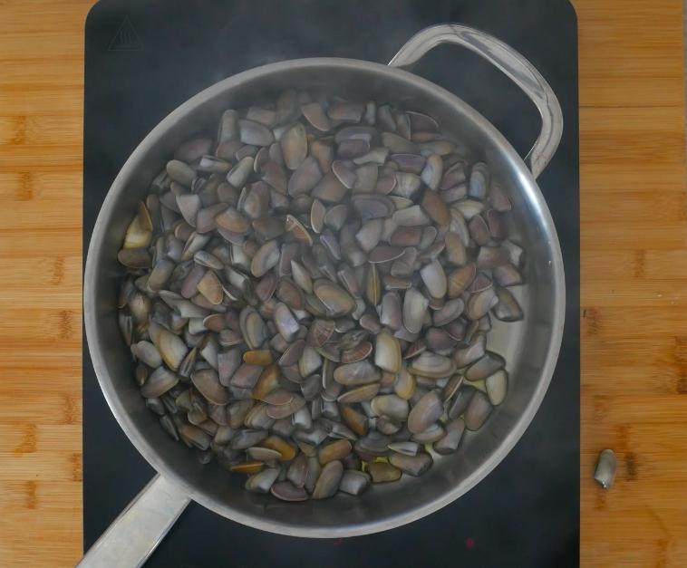 Per prima cosa rosolare con pochissimo olio e 2 spicchi d'aglio le telline. Bagnare poi con 100 ml di Franciacorta, coprire e cuocere per qualche minuto.