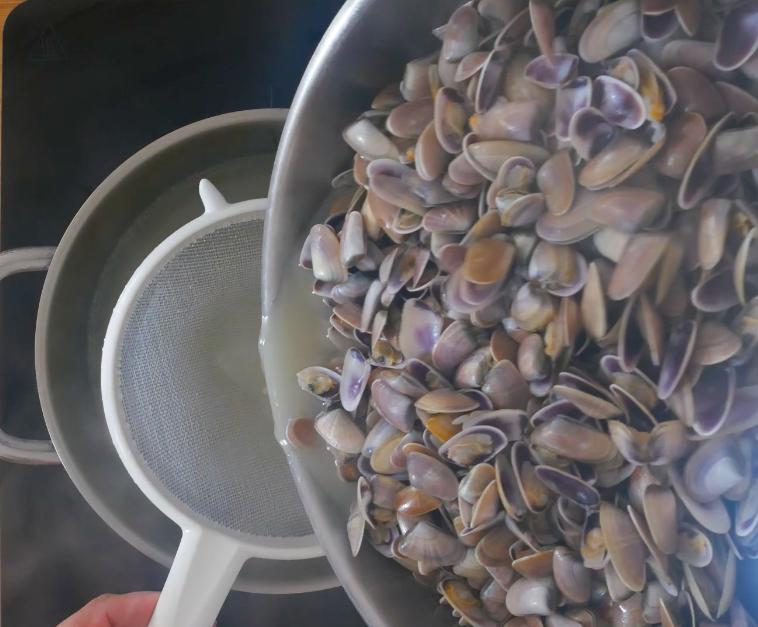 Filtrare l'acqua di cottura delle telline e unirla al brodo di pesce che useremo per cuocere il riso. Sgusciare tutte le telline.
