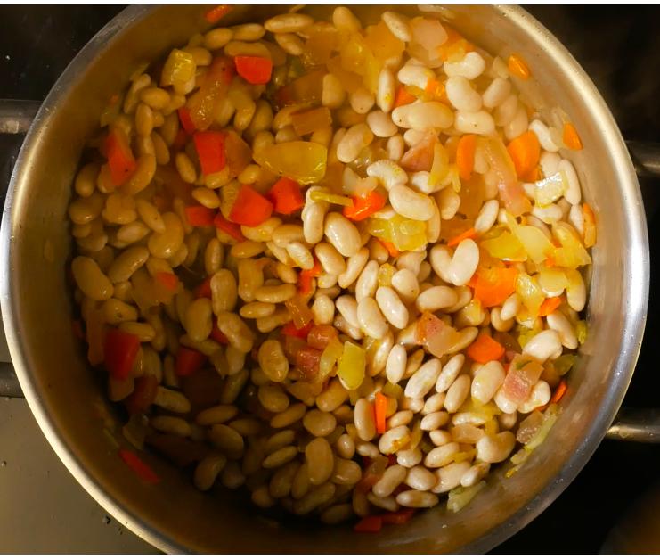 Aggiungere i fagioli scolati dalla loro acqua (dopo essere stati a bagno una notte intera in frigo) e rosolarli con le verdure.