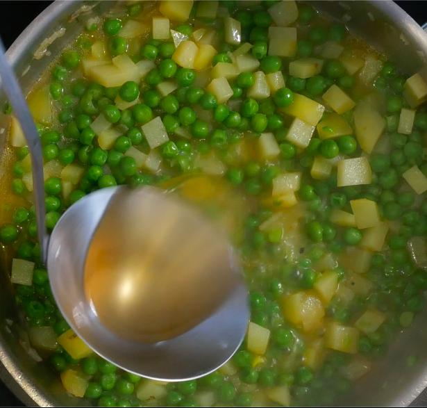 Aggiungere al soffritto piselli e patate e cuocere tutto con il brodo vegetale. Una volta pronto frullare poi il tutto con un minipimer.