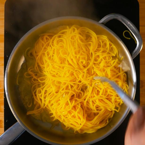 In una pentola capiente bollire l'acqua salata, buttare i tonnarelli e scolarli leggermente al dente e mantecarli con la salsa di carciofi.