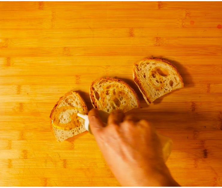 Tostare del pane, condirlo con olio EVO e aromatizzarlo alle erbe.